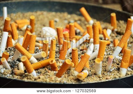used yellow - white cigarettes in old ashtray