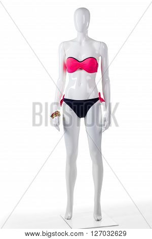 Pink and black swimsuit. Female mannequin in bicolor swimwear. Woman's bright beachwear with bracelets. Fashionable swimsuit in outlet shop.