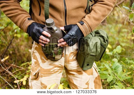 Soldier in a wild forest with flask.
