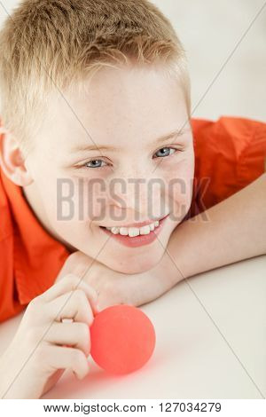 Smiling Boy Leans On Arm And Holds Red Ball