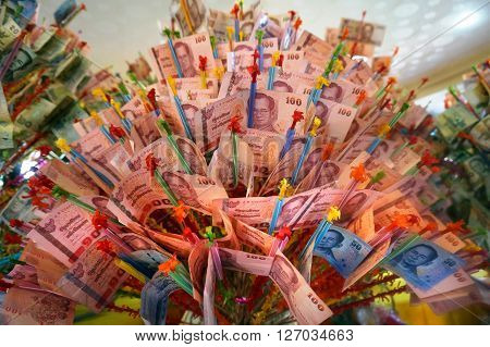Money tree full of Thai banknotes at a buddhist temple. Donations are made by visitors to support monks and receive merit.