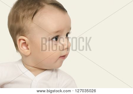 Adorable baby portrait looking curious isolated on white.