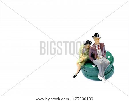 Miniature Man And Woman Sitting On Poker Chips Isolated On White With Room For Copy Space, Gambling