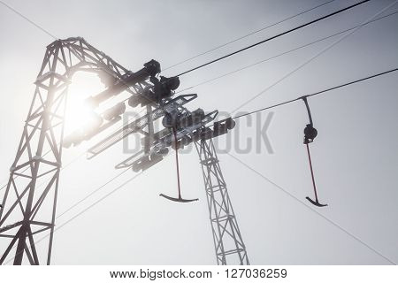 View of a ski lift silhouette against the sun