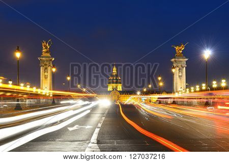 Alexandre III bridge night view with Napoleon's tomb and light trail in Paris, France.