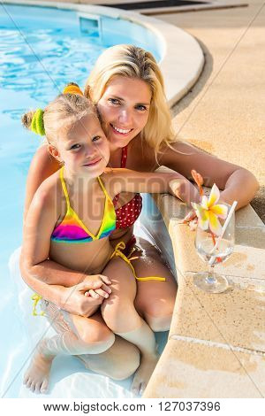 Cute Girl And Beautiful Mother At The Pool