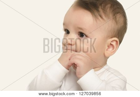 Adorable baby portrait with the hand in the mouth. Cute baby boy looking to the side curious. Isolated on white.