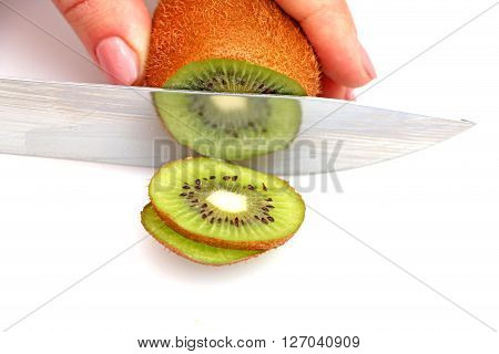 sliced kiwi on a steel knife particles displaying pieces of kiwi cutting one after another in circles