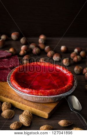 Fresh strawberry pie with nuts on side and frozen berries. Strawberry cake on dark table. Dark and moody style. Magic moon and mistic light