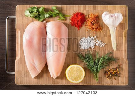 Fresh chicken breast with herbs on a wooden bamboo board. The recipe for the marinade chicken breast. Raw chicken meat on a wooden background.