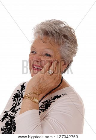 A lovely senior woman in her seventies holding her hand on her face and smiling isolated for white background.