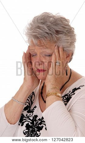 A lovely seventy senior woman holding her hands on her head for severe headache isolated for white background.