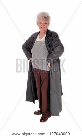 A older senior citizen woman standing isolated for white background in a dark gray coat with her hands on the hips.