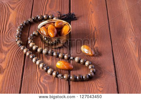 Dates fruit and rosary still life, on a brown wooden background.