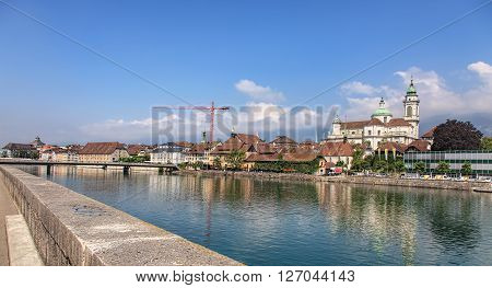 Solothurn, Switzerland - 19 July, 2013: with Aare river and the St. Ursus cathedral. Aare is the longest river that both rises and ends entirely within Switzerland. The St. Ursus Cathedral is a Swiss heritage site of national significance.