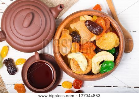 Bowl with dried fruit and tea-things. Flat lay Rural style close up small depth of sharpness