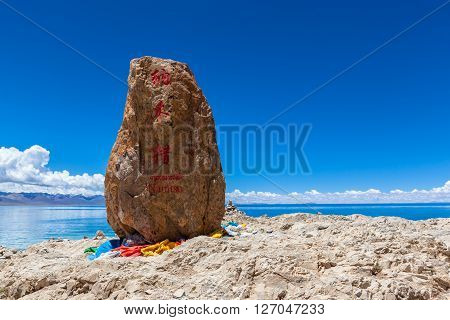 Namtso Lake in Tibet China. The name of the lake (Namtso) is carved in the rock in three languages: Chinese Tibetan and English.