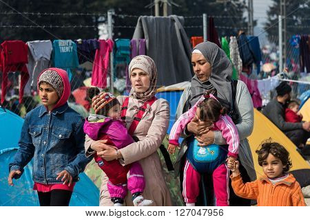 EIDOMENI, GREECE - MARCH 17, 2015: Two women walk with their children on March 17, 2015 in the refugee camp of Eidomeni, Greece. For several weeks more than 10.000 refugees and immigrants wait here for the borders to open.
