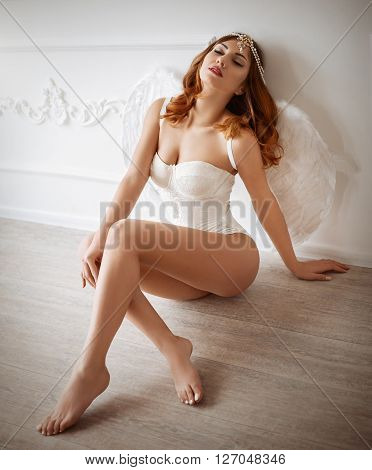 Sexy beautiful brunette girl in white underclothes with wings