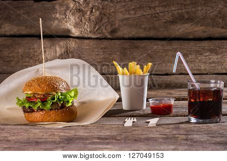 Burger and cola with fries. Burger with ketchup and drink. New breakfast menu in cafe. Enough to feel satiety.