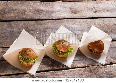Burgers on white wrappers. Variety of hamburgers on table. Choose between beef and ham. Special prices for traditional burgers.