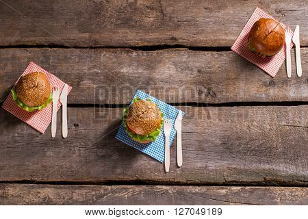 Burgers on sticks with cutlery. Cutlery with hamburgers on table. New recipe of grilled burgers. Food popular among cafe clients.
