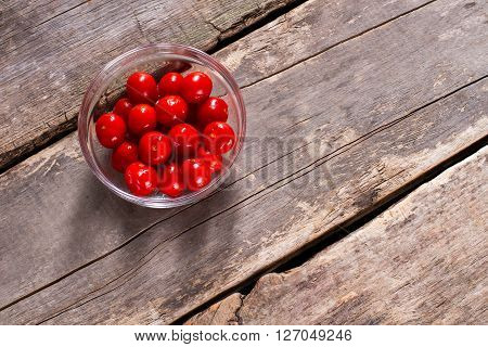 Tomatoes in glass bowl. Tomatoes on brown wooden backround. Fresh juicy vegetables. Ingredient for a salad.
