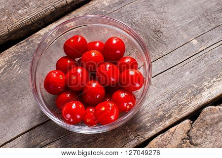 Red tomatoes in glass bowl. Bowl of small tomatoes. Vegetables filled with vitamins. Value your health.