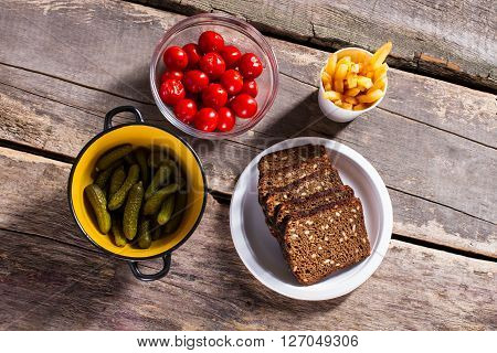 Bread with fries and tomatoes. Pickles and bread on table. Fresh vegetables and brown bread. Ingredients for breakfast.
