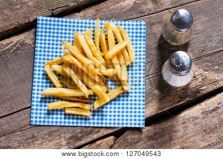 Fries on napkin and pepperbox. Table with spices and fries. Fries at fast food restaurant. Simple old recipe.