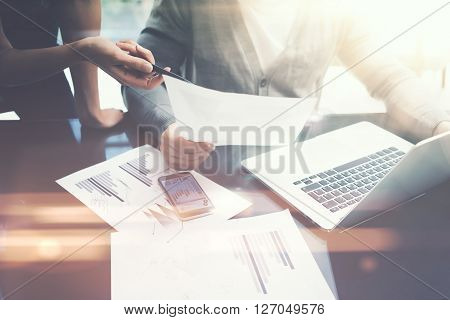 Business situation.Meeting of financial analysts.Photo female showing document.Man holding report and using laptop.Working process modern office, discussion startup. Horizontal.