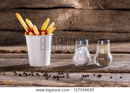 Cup of fries with pepperbox. Salt, pepperbox and fries. Fast food snack on table. So fresh and crispy.