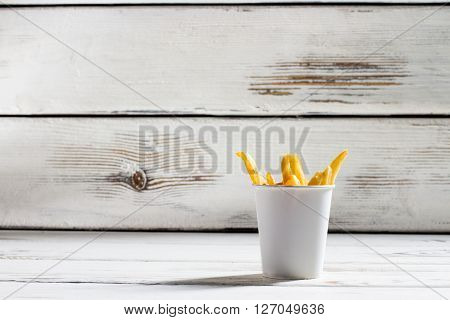 Cup of french fries. White table with fries cup. Crispy and delicious food. High-fat snack in bistro.