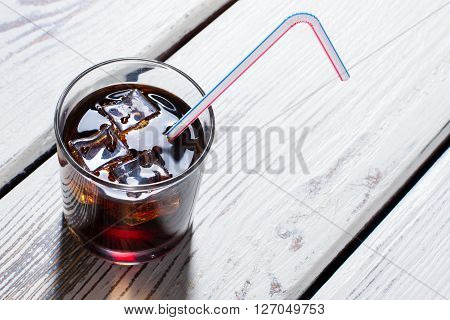 Glass of cola with tube. Ice cubes in cola glass. Dark drink on white table. Popular non-alcoholic beverage.