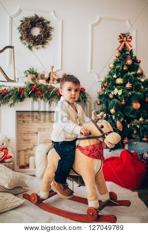 Baby boy with toy horse near Christmas tree