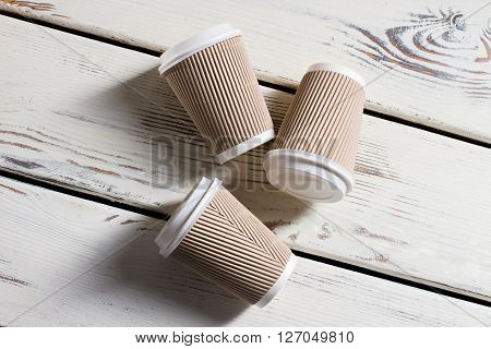 Laying ripple paper cups. Hot drink cups with lids. Disposable cups on white table. Running out of coffee.