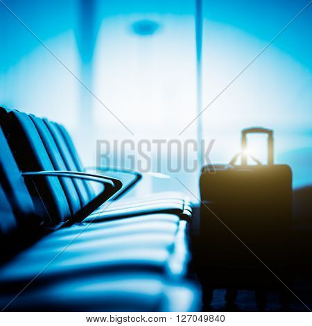 Empty seat and a luggage in airport,blue toned.