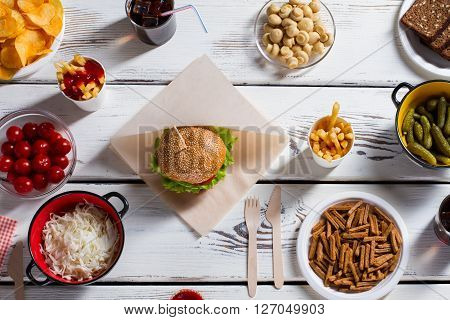 Burger and chips with pickles. Sauerkraut, tomatoes and burger. White table with food set. Vacation lunch idea.