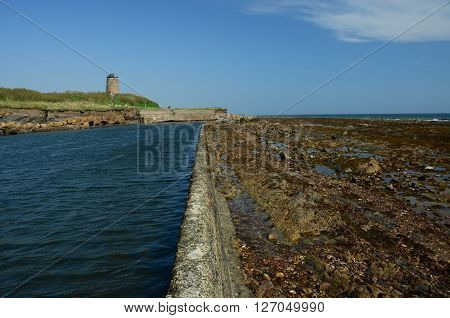 An outdoor pool and windmill on the coast at St. Monans