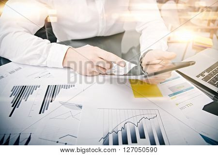 Picture man touching modern tablet screen.Investment manager working new private banking project office.Using electronic device.Graphic icons, stock exchanges reports table. Film effect