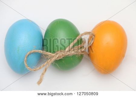 Easter yellow,green, blue  eggs tied up by a thread.