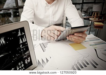 Photo businessman touching modern tablet screen.Using electronic devices.Graphics icons, worldwide stock exchanges notebook.