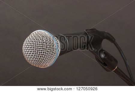 Clean shot of a microphone (mic) against a charcoal background ready to be grabbed and used.