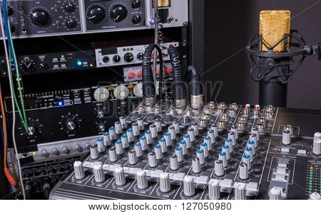Recording studio mixing console with microphone and studio equipment in the background.