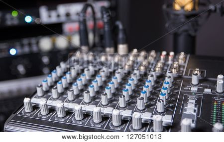 Artistic shot of recording studio mixing board and equipment in the background.