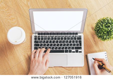 Topview of male hands using blank white laptop on wooden surface with notepad coffee and other items. Mock up