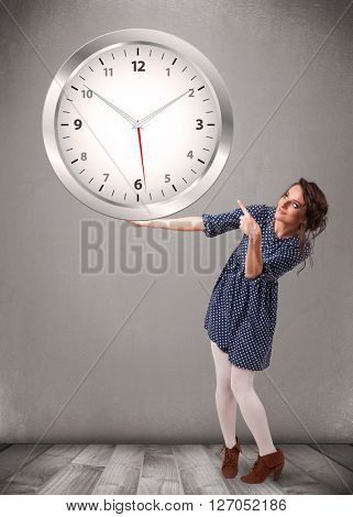 Attractive young lady holding a huge clock