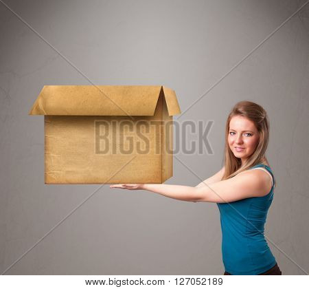 Beautiful young woman holding an empty cardboard box