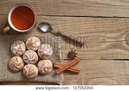 Tea with glazed gingerbread cookies on old wooden table background. Top view
