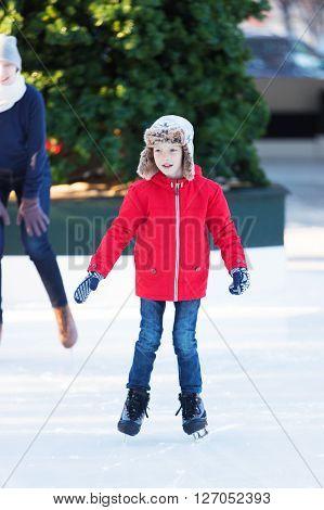 smiling positive boy enjoying ice skating at outdoor skating rink winter holiday or vacation activity